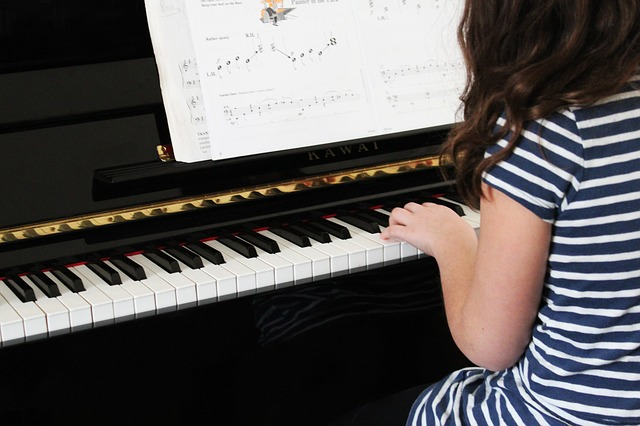 girl taking music lessons on piano